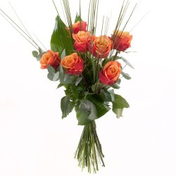 oranger Rosen mit dekorativen Grün arrangiert