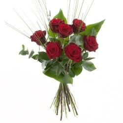 rote Rosen mit dekorativen Grün arrangiert